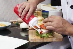 Chef, der Tomatensauce zum Hamburger setzt lizenzfreie stockfotografie