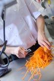 Chef in der Uniform, die frische Karottentaktstöcke vorbereitet Stockbilder