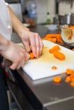 Chef in der Uniform, die frische Karottentaktstöcke vorbereitet Stockfotografie