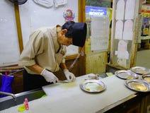 Chef in der Uniform, die Sushi und Sashimi zubereitet stockbilder