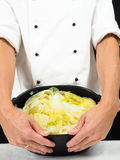 Chef in der weißen Jacke, die um eine Kasserolle des gekochten cabbag hält Lizenzfreies Stockfoto
