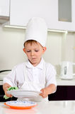 Chef des kleinen Jungen, der seine Platten beim Kochen säubert Lizenzfreie Stockbilder