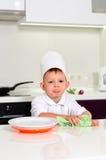Chef des kleinen Jungen, der seine Platten beim Kochen säubert Stockbild
