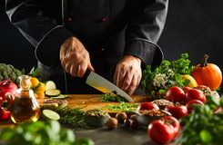 Chef dicing fresh herbs with a kitchen knife. Chef dicing fresh herbs on a wooden chopping board with a kitchen knife while preparing salad in a close up on the stock photography