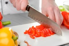 Chef dicing a red pepper. Chef dicing a red bell pepper with a sharp santoku knife. Cooking, healthy eating, vegetarian food stock photo