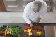 Chef Dicing Red And Yellow Bell Peppers. High angle view of male chef dicing red and yellow bell peppers in commercial kitchen stock images