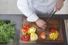 Chef Dicing Red And Yellow Bell Peppers. Midsection of male chef dicing red and yellow bell peppers in commercial kitchen stock photos