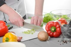Chef dicing spring onions. Cutting bell peppers and mushrooms for a stir-fry dish. Process of cooking a delicious food stock image