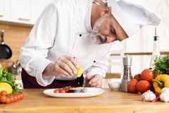 Chef with diligence finishing dish on plate, fish with vegetables royalty free stock photography