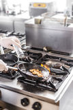 Chef doing flambe. To food in pan with alcohol in big flame Royalty Free Stock Photography