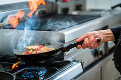 Chef doing flambe to food in pan with alcohol Stock Photography