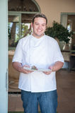 Chef in a doorway. Chef in the doorway of his restaurant holding a plate of food Stock Photo
