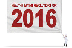 Chef drags flag of healthy eating resolutions. Picture of Asian female chef wearing uniform and drags a big flag of healthy eating resolutions for 2016 Royalty Free Stock Image