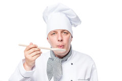 Chef eating a dish on a wooden spoon on a white Royalty Free Stock Image