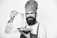 Chef eats italian or asian noodles. Traditional menu concept. Man with beard holds tasty dish on white background. Cook with smiling face in burgundy uniform stock image