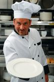 Chef with empty plate. Attractive Caucasian chef holding an empty plate in a commercial kitchen Royalty Free Stock Photography
