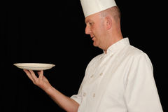 Chef with empty plate. A chef looking at an empty plate he is holding Royalty Free Stock Photography