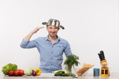 Chef. Enjoying in his kitchen isolated on white. Man with pan on his head in blue shirt smiling and and going to prepare smth with fresh vegetables Royalty Free Stock Photos