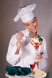 Chef Enjoys Valentine Dessert. Close up of an attractive female Dessert Chef eating an elegant Valentine's day cherry dessert with white and dark chocolate Royalty Free Stock Photography