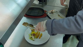 Chef explaining cook trainee how to put fish on a plate with vegetables stock video footage