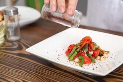Chef féminin ajoutant des épices au plat savoureux du plat Photographie stock