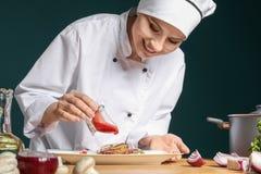 Chef féminin dans l'uniforme ajoutant la sauce au plat savoureux Photo libre de droits