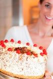 Chef féminin de boulanger ou de pâtisserie avec le torte photo stock