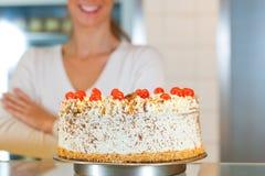Chef féminin de boulanger ou de pâtisserie avec le torte Image stock