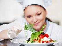 Chef féminin de cuisinier décorant la nourriture préparée de salade photos libres de droits