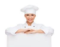 Chef féminin de sourire avec le conseil vide blanc Photo stock