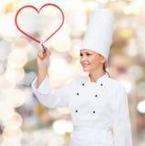 Chef féminin de sourire dessinant le coeur rouge sur l'air Photos libres de droits