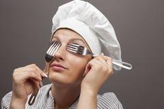 Chef féminin regardant par des fourchettes Photos libres de droits