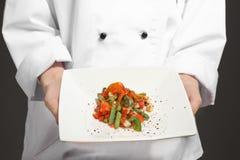 Chef féminin tenant le plat avec le plat savoureux Photos stock