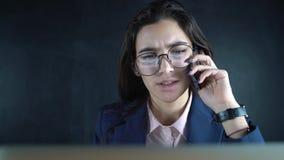 Chef för ung kvinna som talar vid mobiltelefonarbete på bärbara datorn i affärskontor Affärskvinna som använder mobilen för lager videofilmer