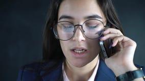 Chef för ung kvinna som talar vid mobiltelefonarbete på bärbara datorn i affärskontor Affärskvinna som använder mobilen för stock video