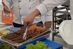 Chef für das Kochen von Würsten und von gegrilltem Fleisch Stockfoto