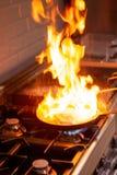 Chef faisant cuire avec le feu élevé dans la cuisine Image stock