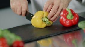 Chef faisant cuire la nourriture au restaurant de cuisine Les mains de chef de plan rapproché coupent en tranches le poivre jaune clips vidéos