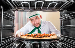 Chef faisant cuire la pizza dans le four Photos stock
