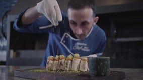 Chef faisant cuire le plat savoureux dans la fin moderne de restaurant  Homme dans l'uniforme de cuisinier arrosant le chiche-keb banque de vidéos