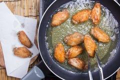 Chef faisant frire des ailes de poulet dans la casserole photo libre de droits