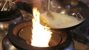Chef faisant frire des légumes avec des nouilles, cuisson professionnelle Repas délicieux banque de vidéos