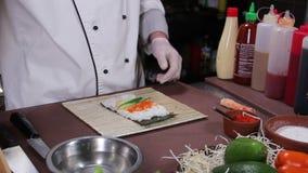 Chef faisant les petits pains de sushi délicieux avec le concombre et le caviar rouge clips vidéos