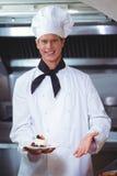Chef fier tenant un plat de désert de gâteau au fromage Photo stock