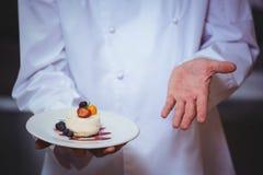 Chef fier tenant un plat de désert de gâteau au fromage Photos libres de droits
