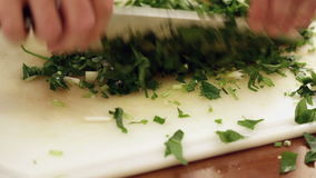 Chef finely chopping parsley or coriander leaves; closeup stock video footage