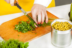 Chef finely shred dill and parsley Royalty Free Stock Photos
