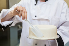 Chef finishing a cake with icing Royalty Free Stock Images