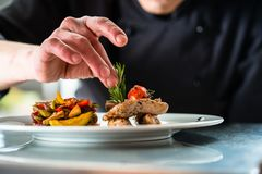 Chef finishing and garnishing food he prepared. A dish with pork meat and vegetables Royalty Free Stock Photos