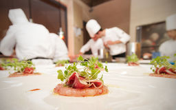 Chef finishing her plate and ready to serve at the table. Finall Royalty Free Stock Images